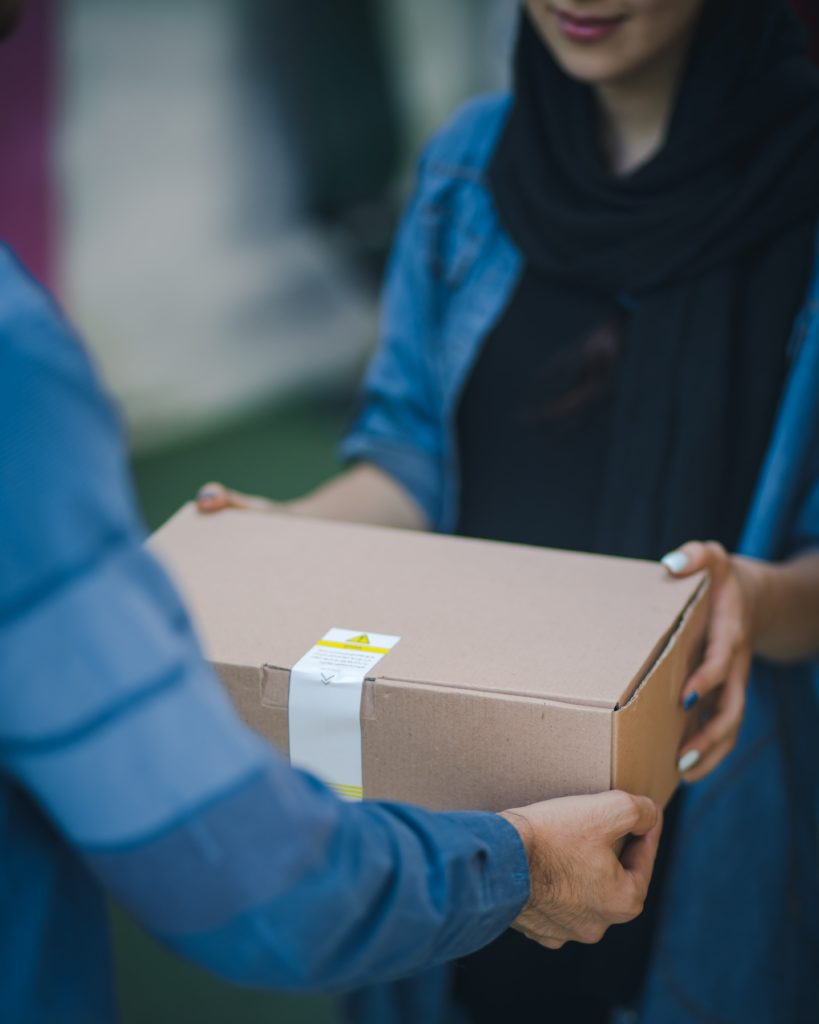 Person handing over brown box