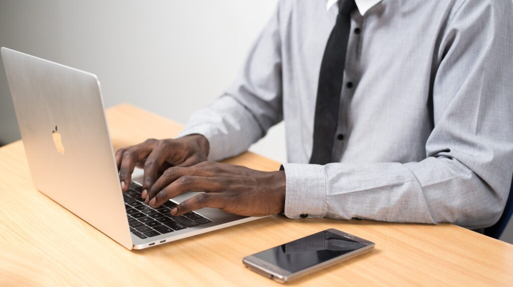 Man sitting at laptop with a mobile phone beside him