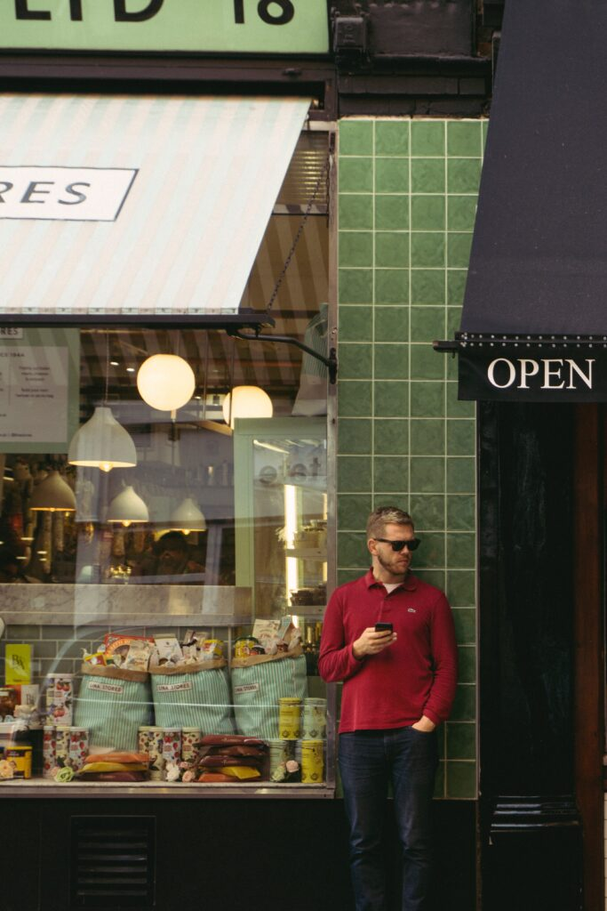 Man using smartphone whilst standing outside of a shop